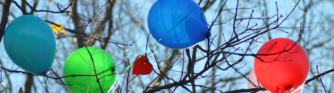 Image of helium balloons caught in a tree.
